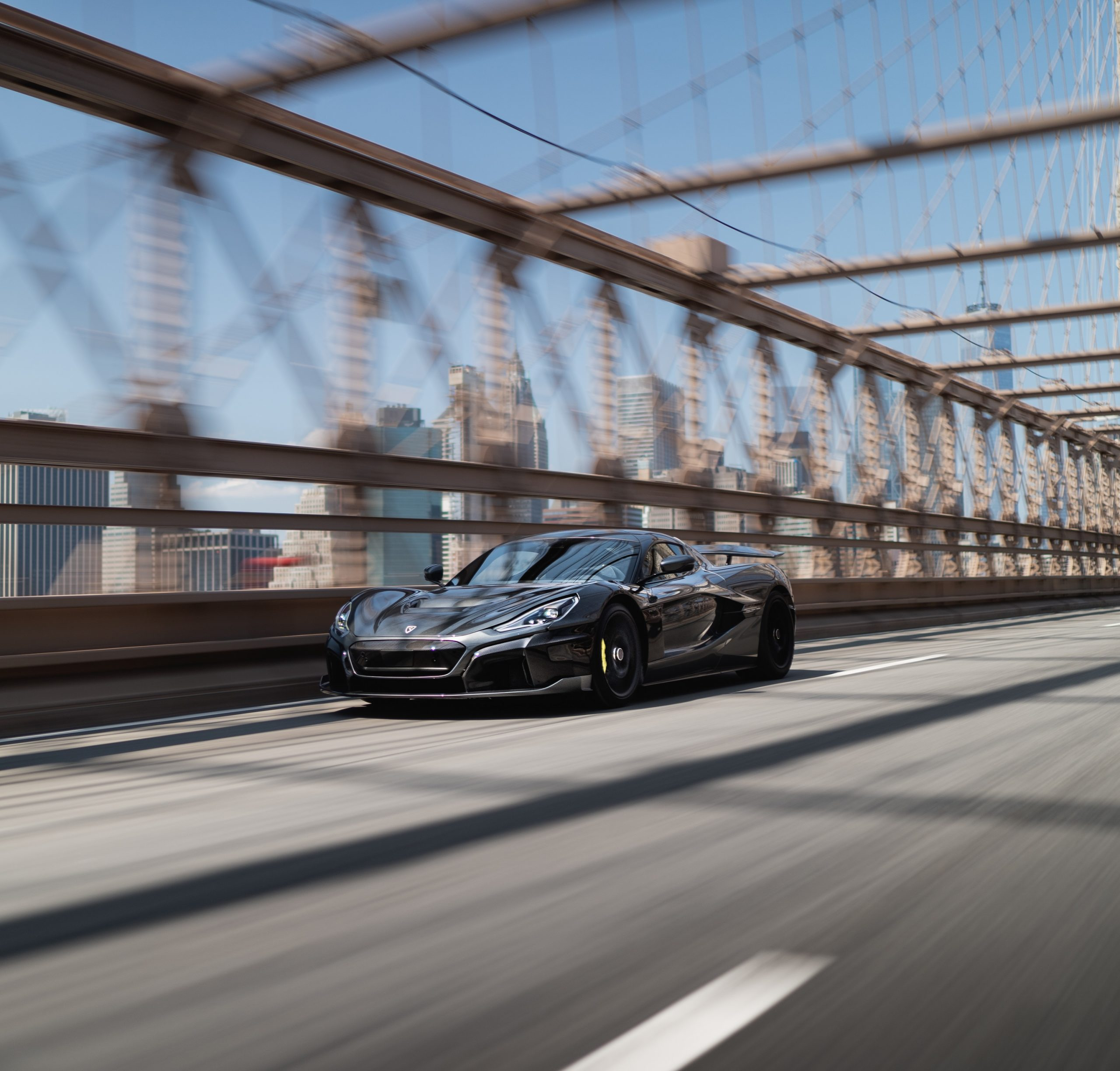 A grey Rimac Nevera, arguably the king of the electric supercars, drives down a bridge shot from the front 3/4.
