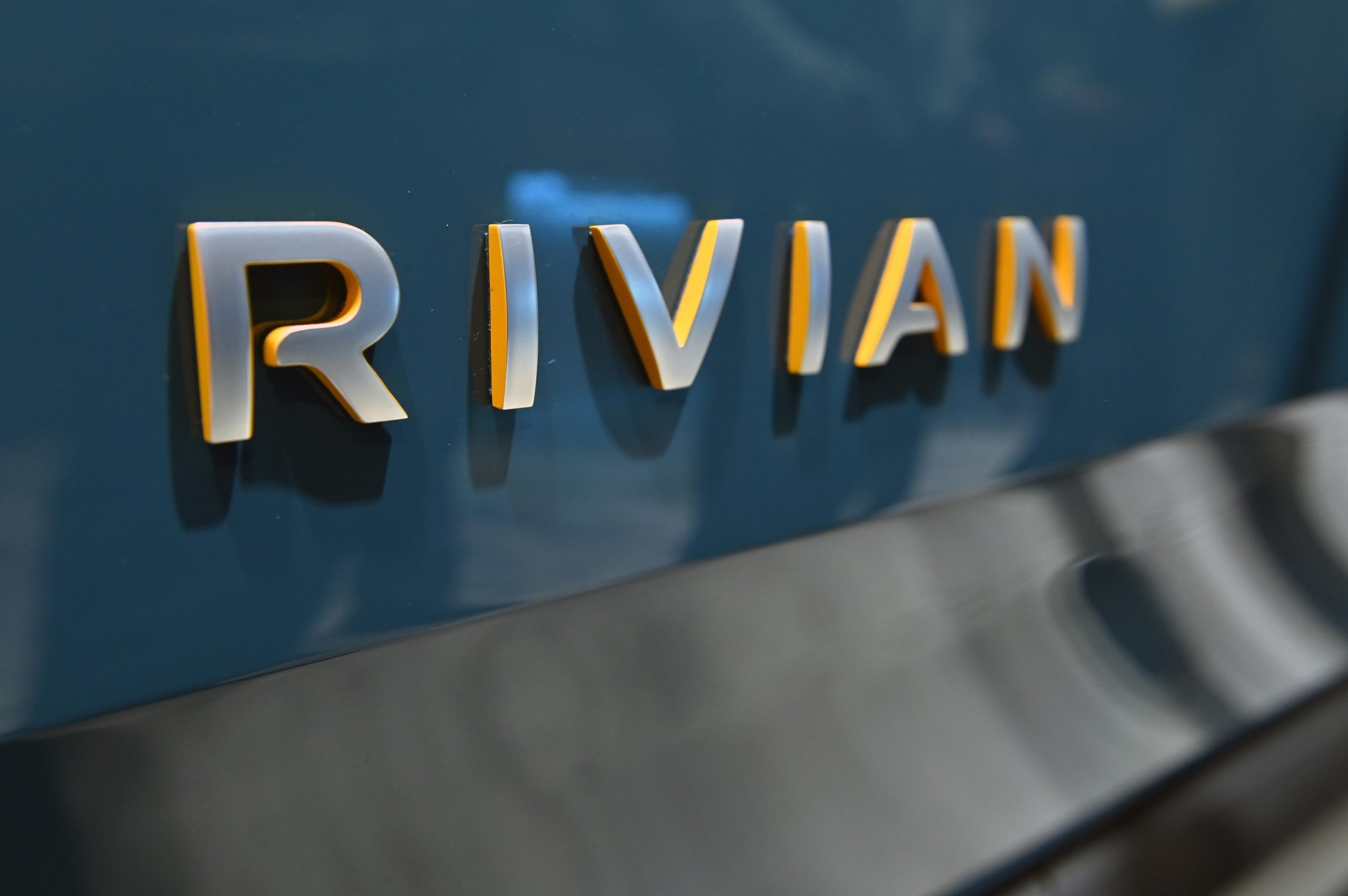 A grey Rivian logo on the back of a blue R1T truck at an auto show