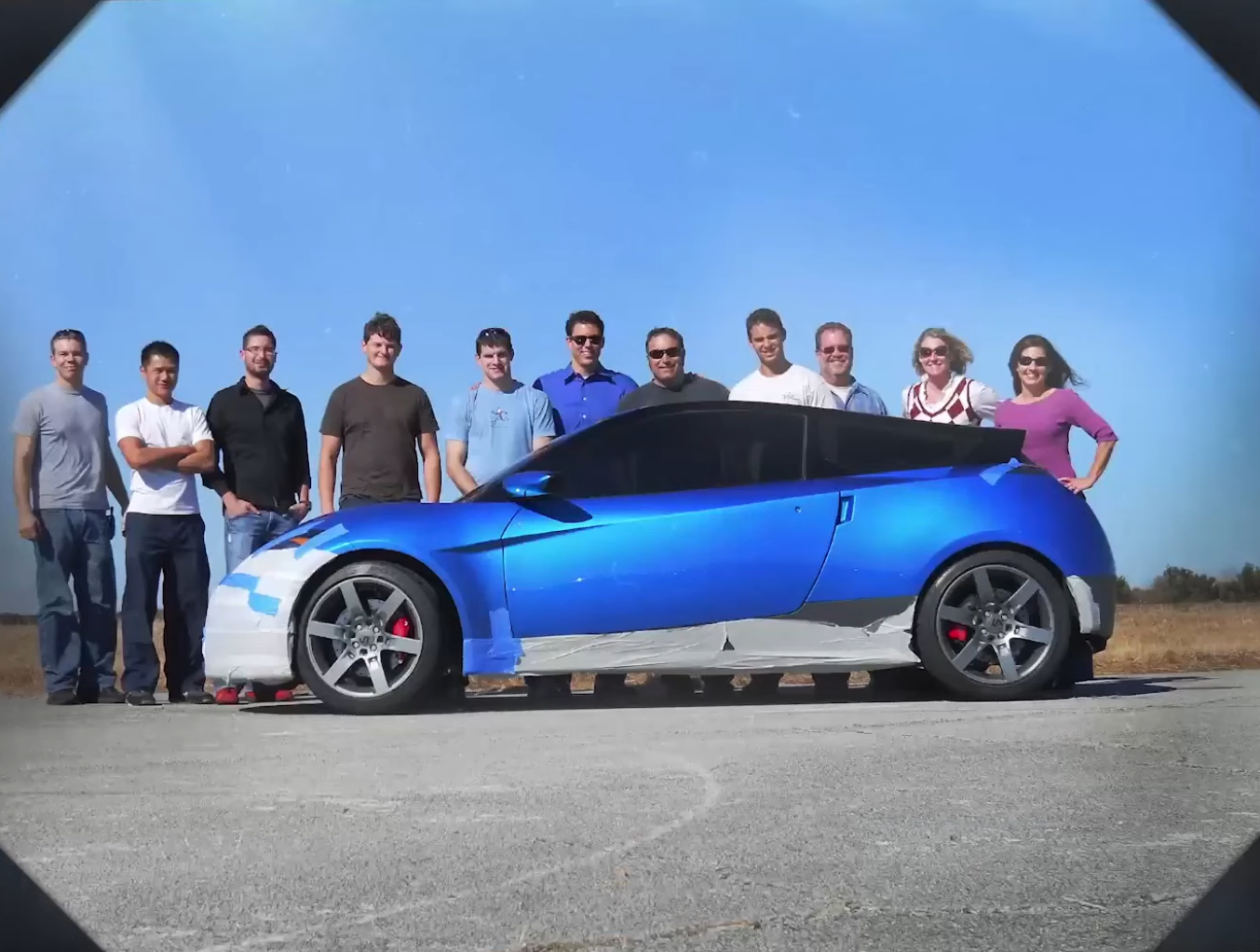 The blue Rivian sports car prototype, shot in profile with employees standing behind it