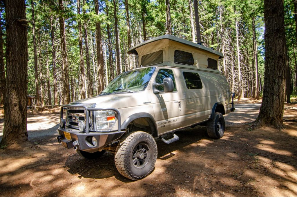 4x4 camper van parked in the woods with the pop-top up