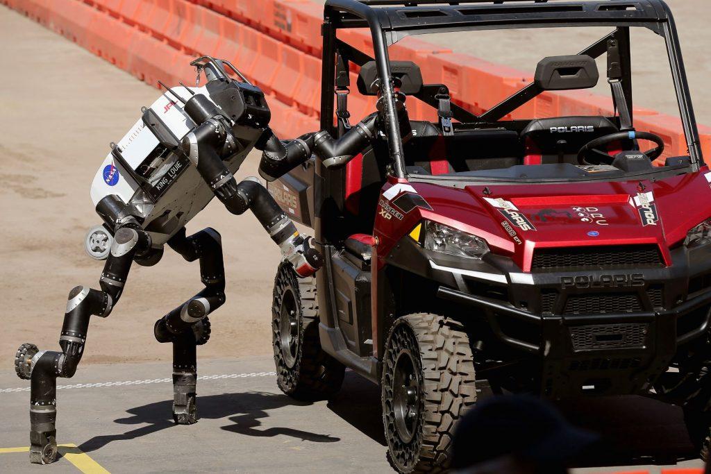 A Nasa robot entering a Polaris vehicle to drive it