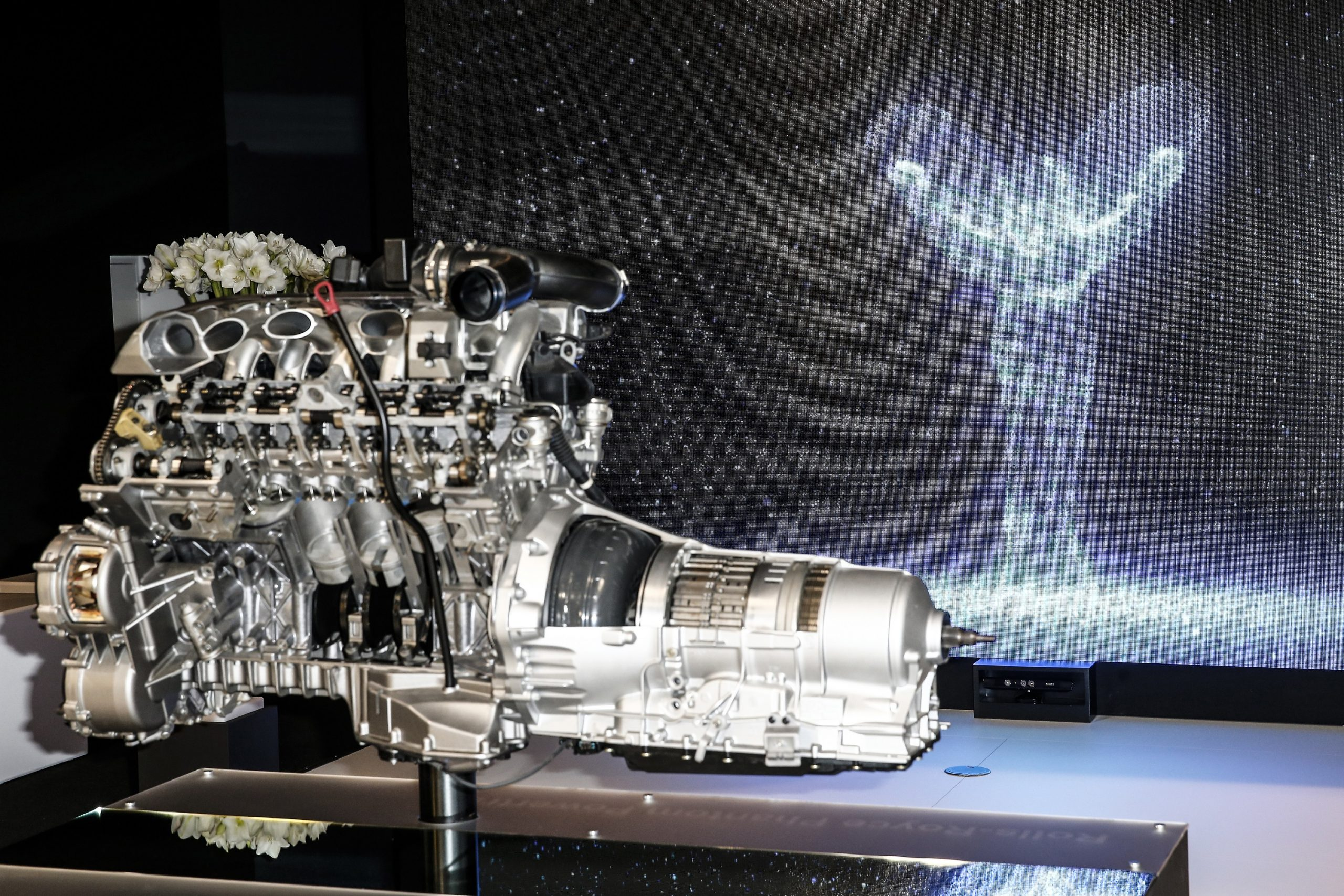 A V12 engine out of one of Rolls Royce's luxury cars on a stand at an auto show