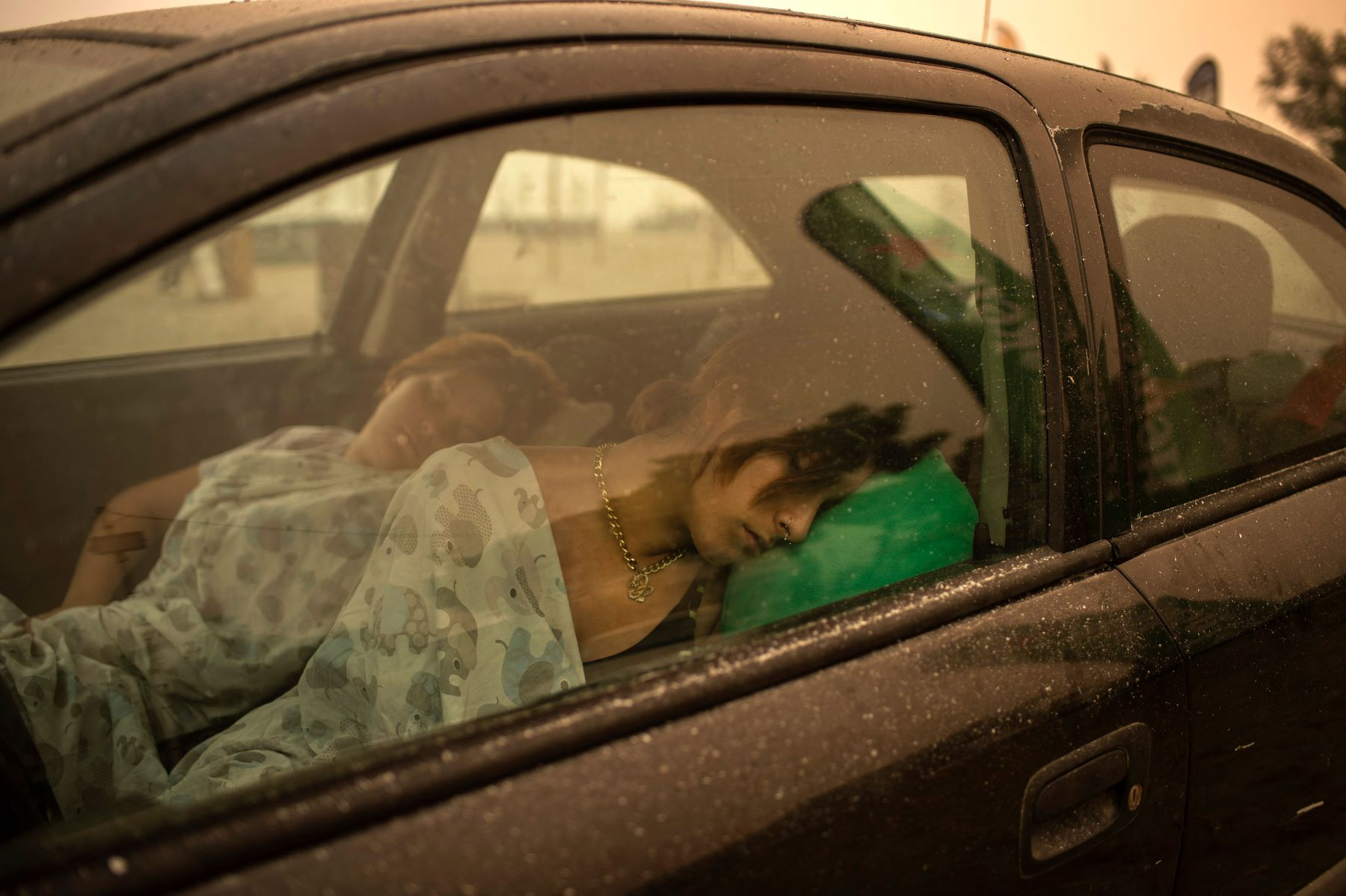 A woman and child sleeping in a car in the Pefki village of Euboea, Italy