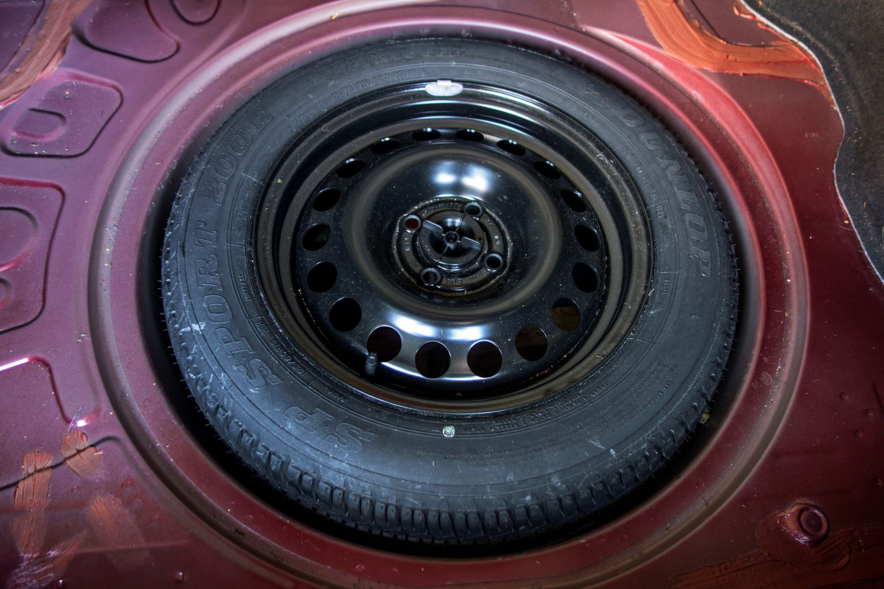 A full-size spare tire stowed in the trunk of a car