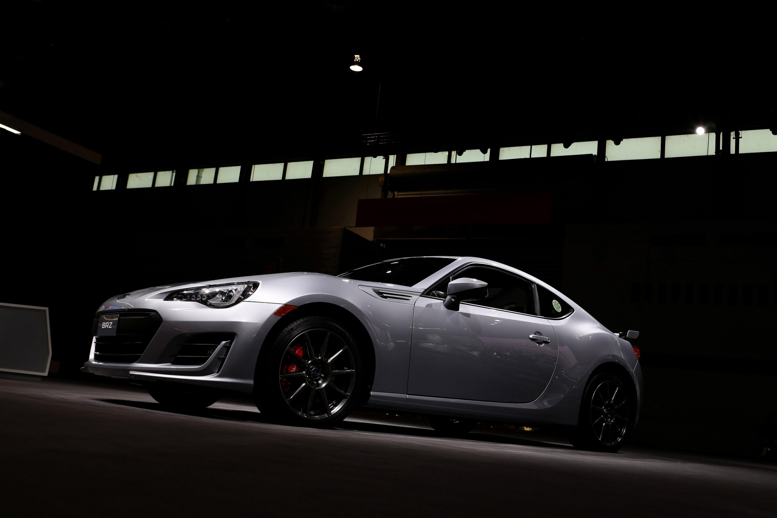 A silver Subaru BRZ seen under a studio light at a warehouse, shot from the low front 3/4 angle