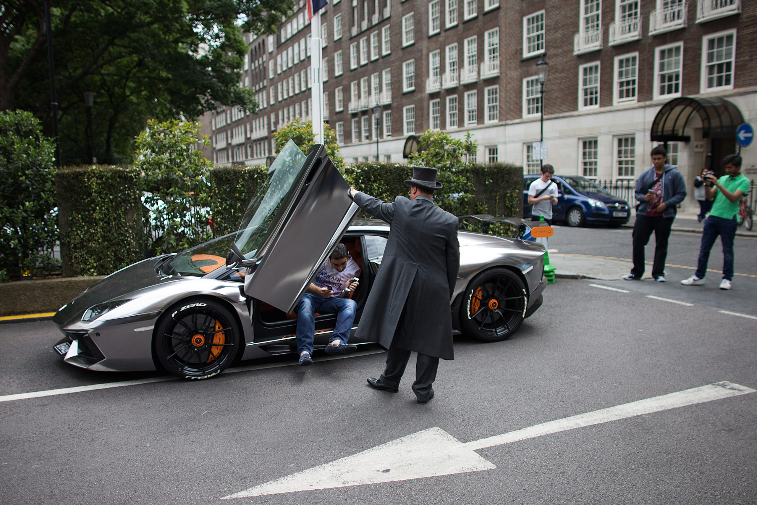 A valet helps an owner out of his silver Lamborghini supercar