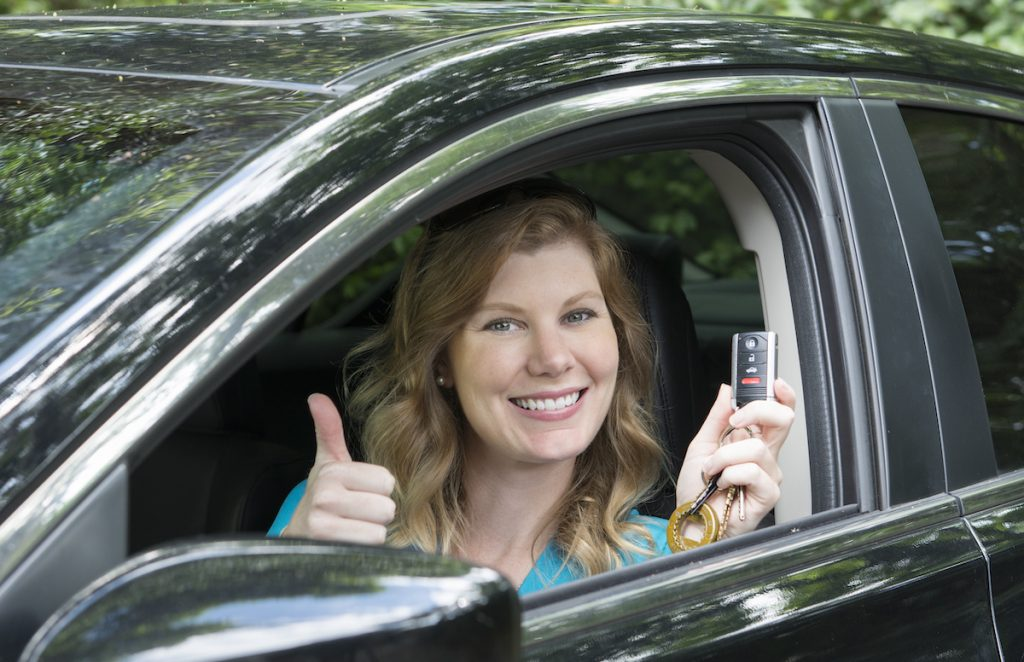 A teen driving a car gives a thumbs-up