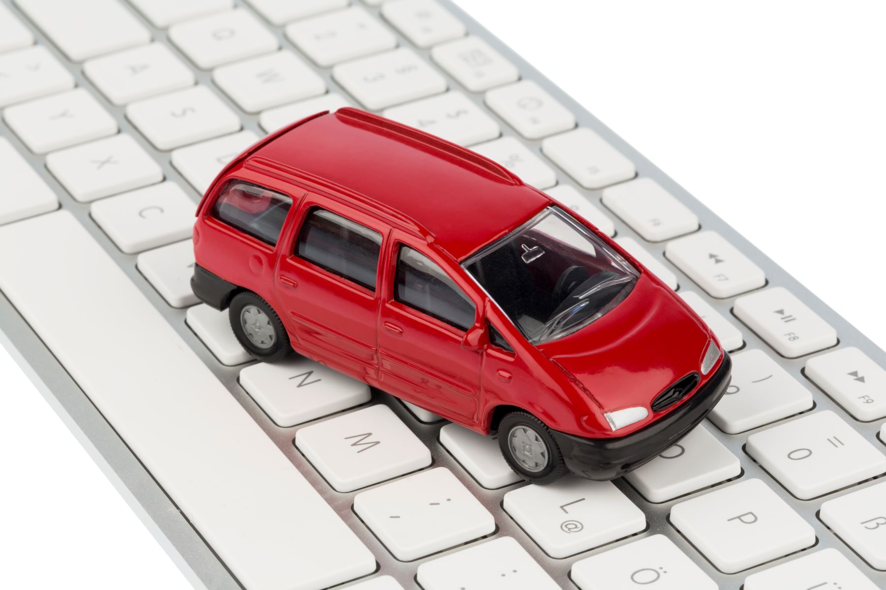A red toy car on a keyboard symbolizing car buying online