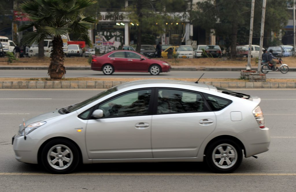 A man driving a hybrid car along the streets of Islamabad