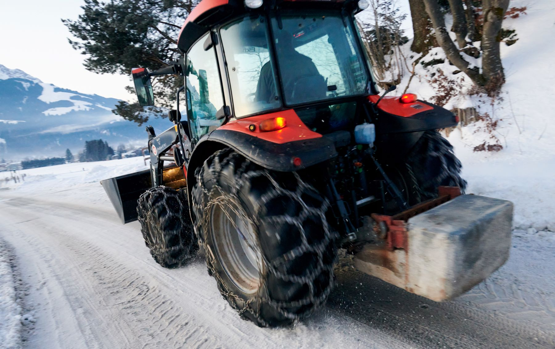 A tractor driving on a snowy road with with snow chains on its tires