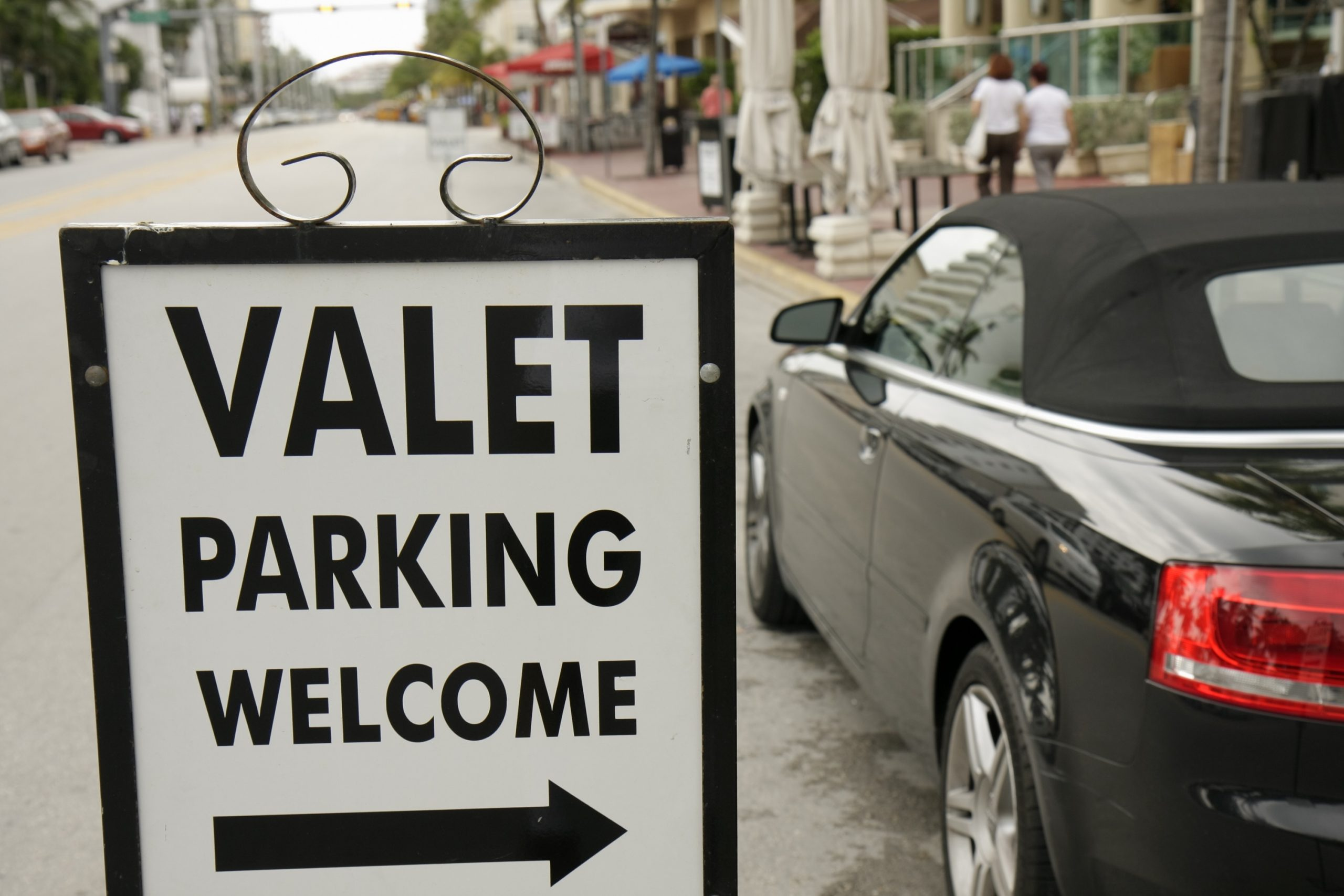 """A white sign that reads """"Valet parking"""""""