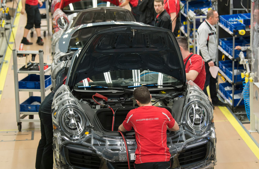 Porsche sportscars are lined up on the assembly line in the factory