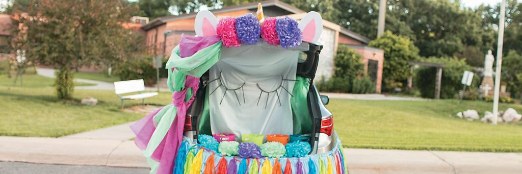 A colorful trunk-or-treat unicorn costume for a car.