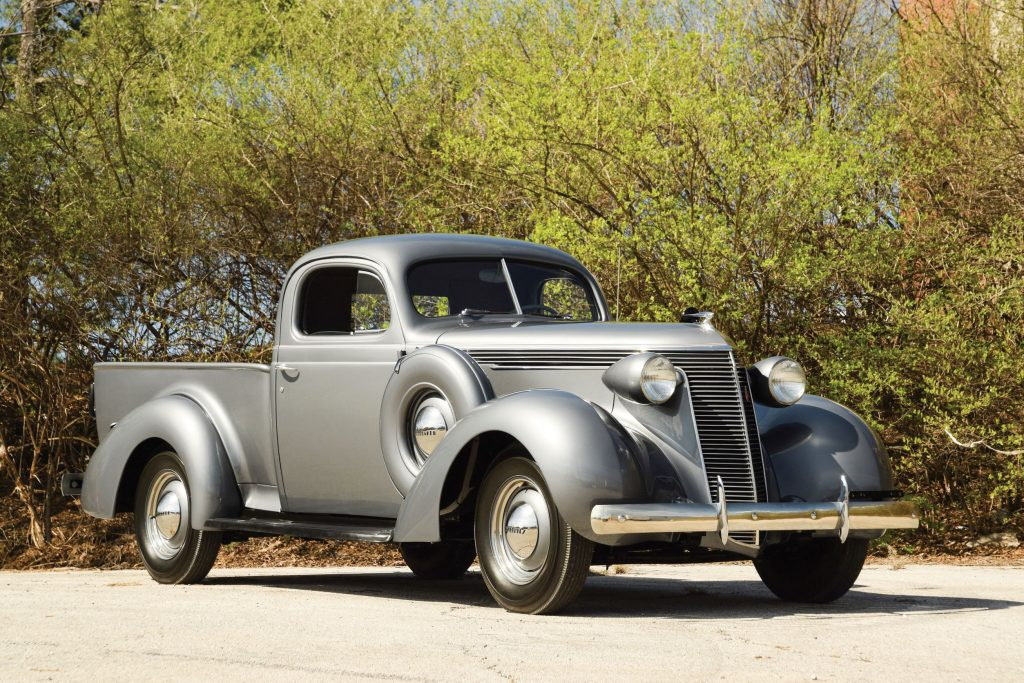 A gray 1937 Studebaker J5 Coupe Express parked by a green hedge