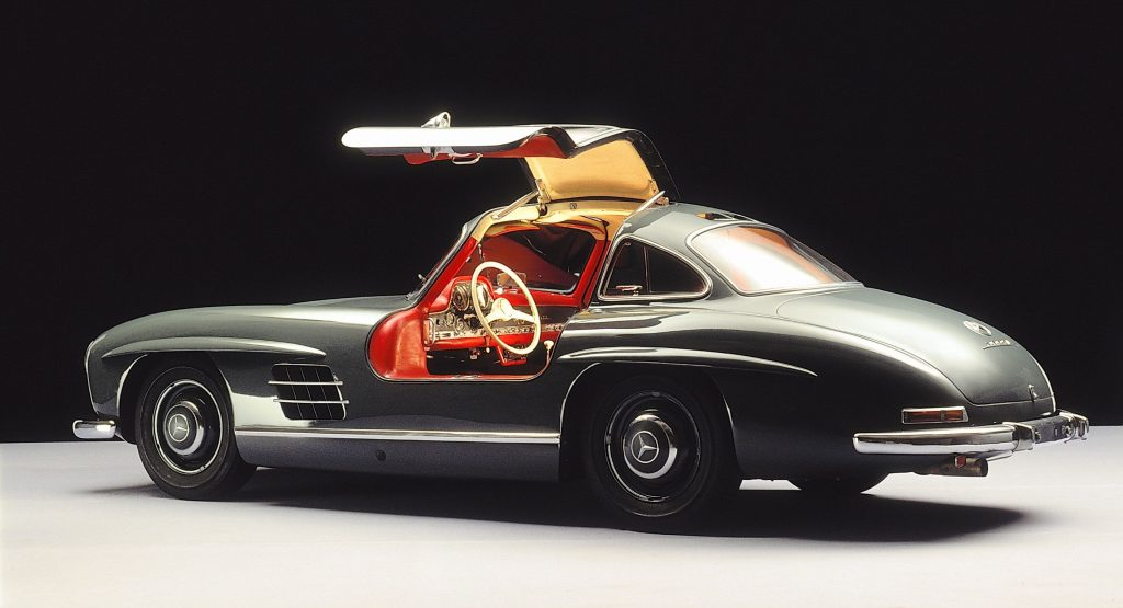 The side 3/4 view of a green 1954-1957 Mercedes 300SL Gullwing coupe with its driver door up