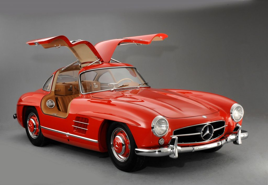A red 1957 Mercedes 300SL Gullwing coupe with its doors up