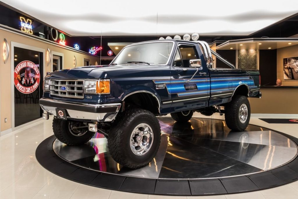 A 1987 Ford F-250 Bigfoot Cruiser parked inside a showroom