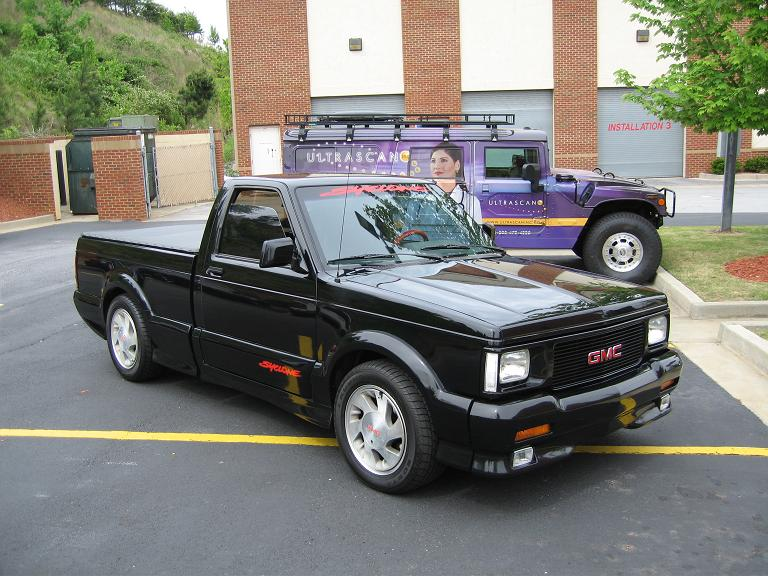 A black 1991 GMC Syclone parked in a parking lot