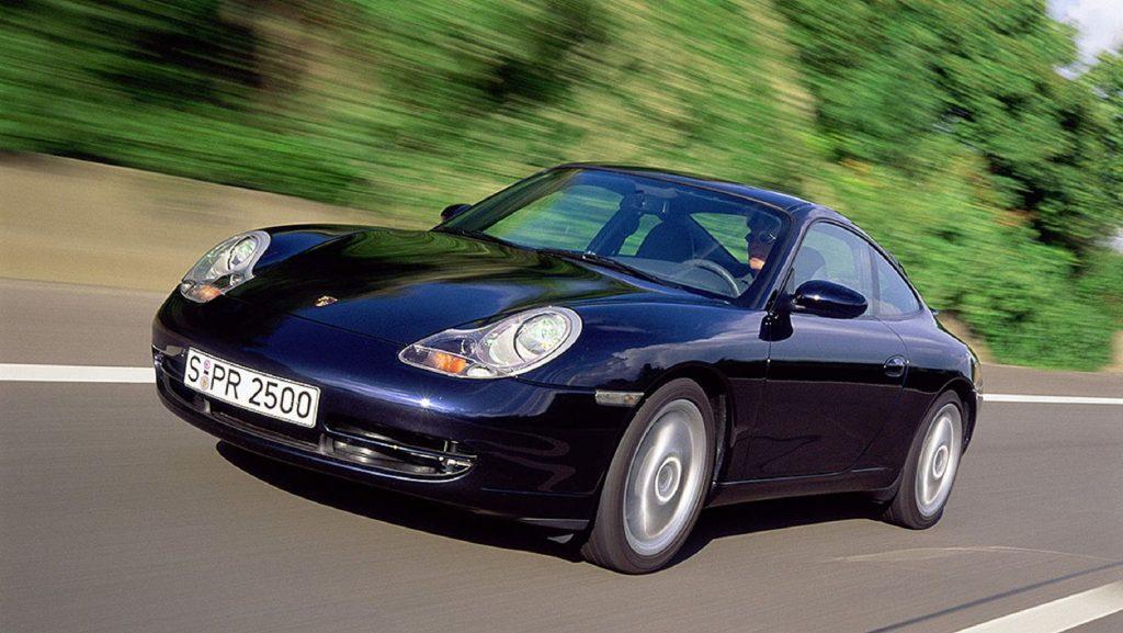 A dark-blue 2001 996 Porsche 911 Carrera driving down a road