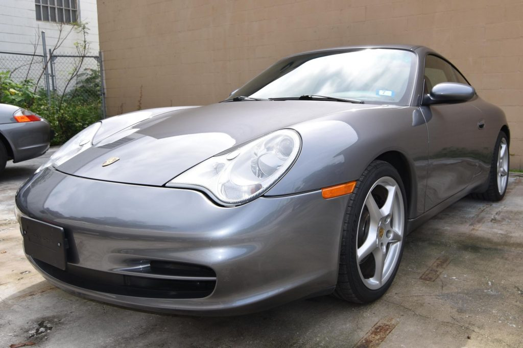The front 3/4 view of a gray 2002 Porsche 911 Carrera in a parking lot