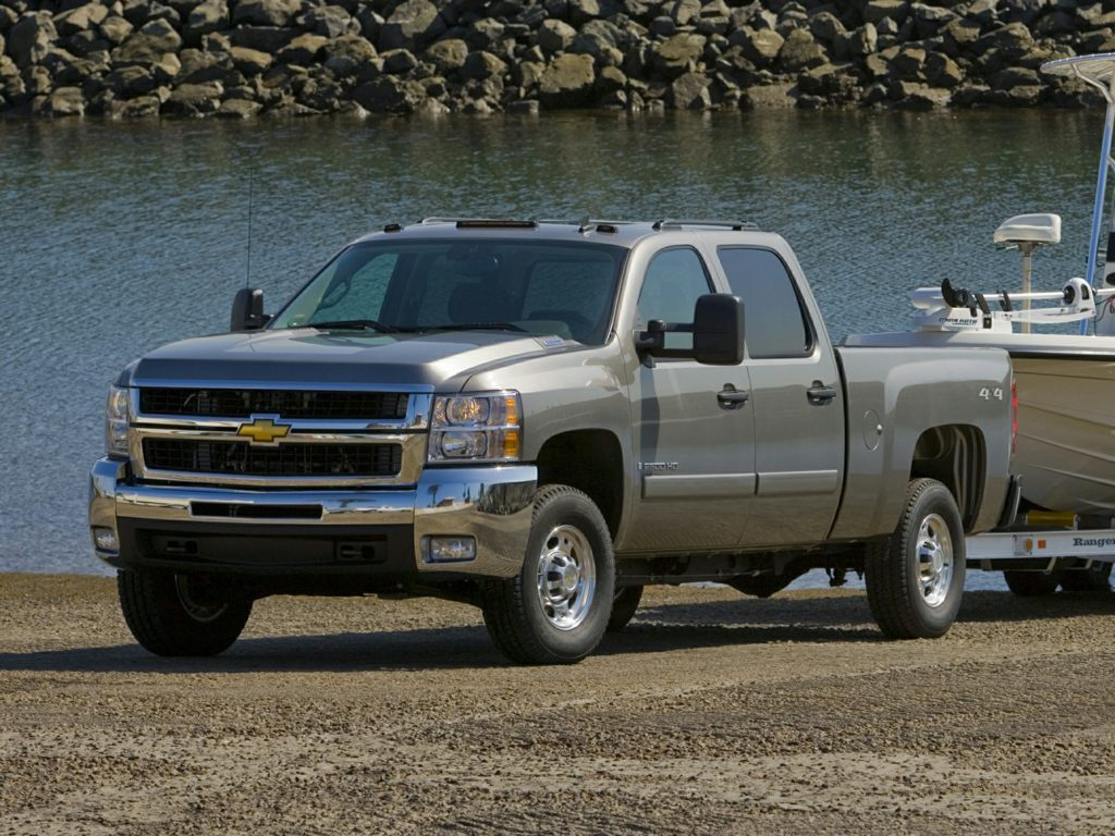 A gray 2009 Chevrolet Silverado 2500 HD pulls a boat out of the water