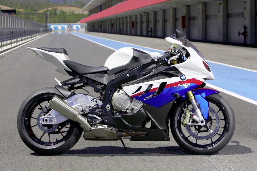 The side view of a white-blue-and-red 2010 BMW S 1000 RR on a racetrack