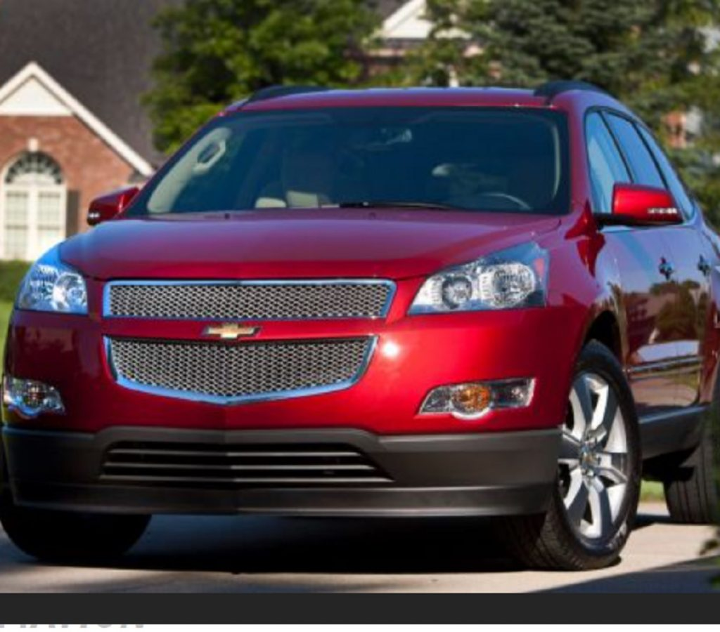 A red 2012 Chevy Traverse parked in a neighborhood.