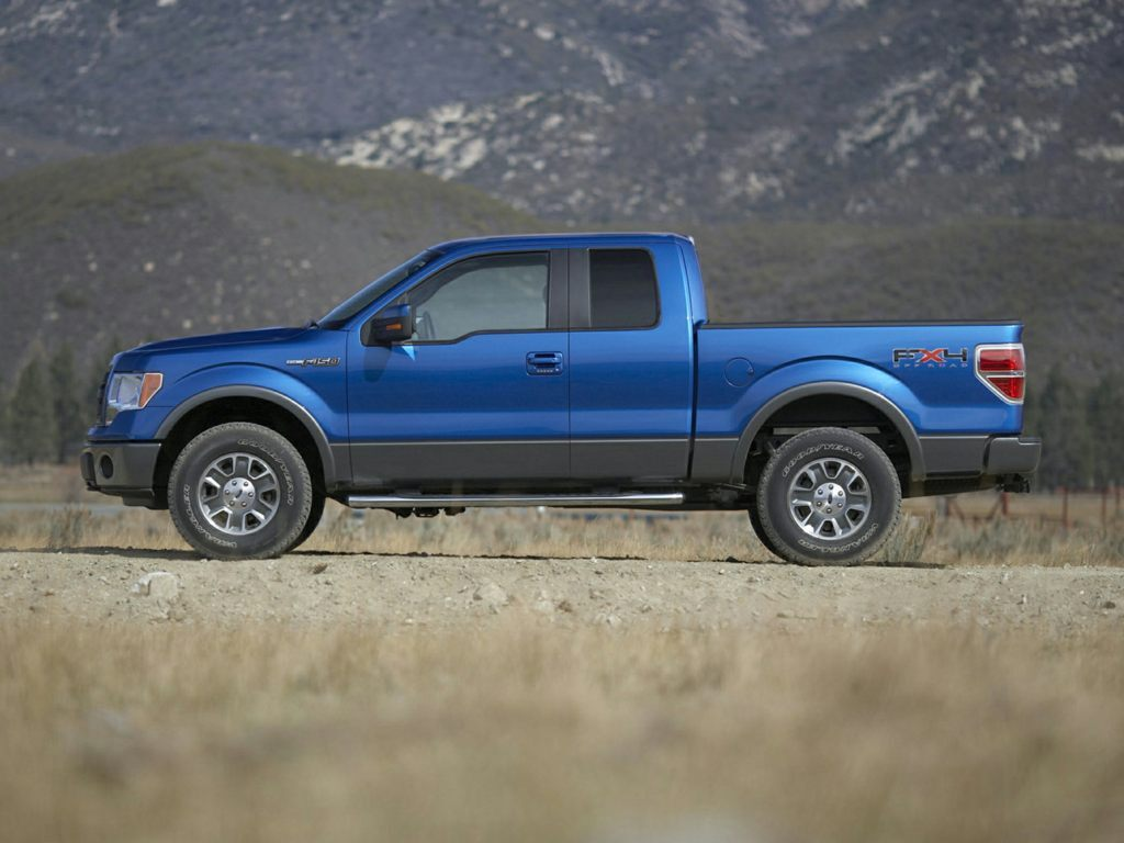 A blue 2012 Ford F-150 parked outside near grass