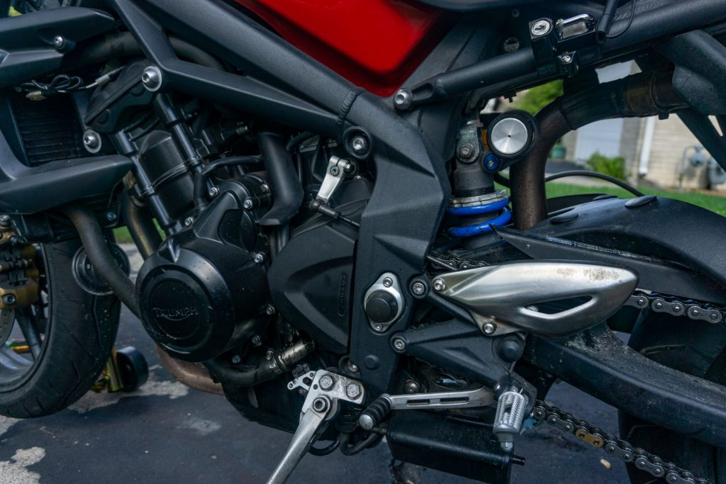 The adjustable rear mon-shock on a red-and-black 2012 Triumph Street Triple R