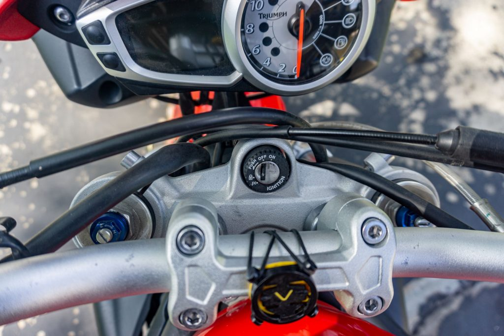 An overhead view of the blue preload adjusters and silver rebound damping adjusters on top of a red 2012 Triumph Street Triple R motorcycle's forks