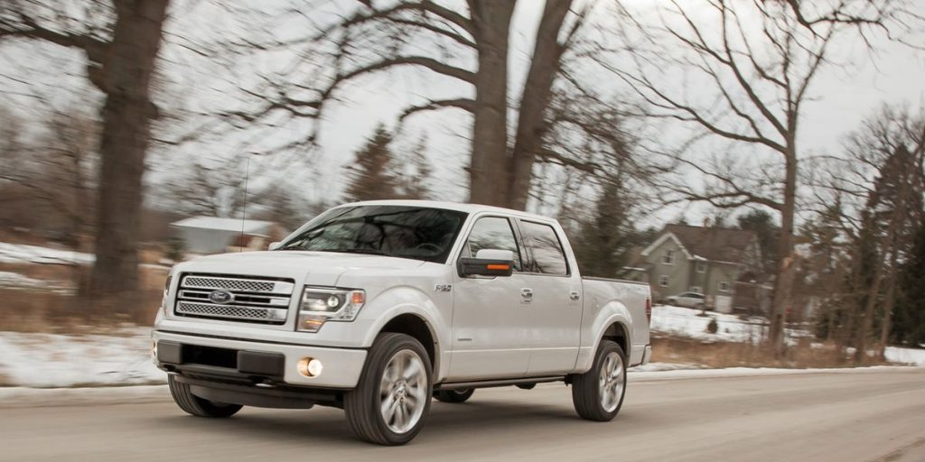 a white 2013 Ford F-150 drives on a road in the snow