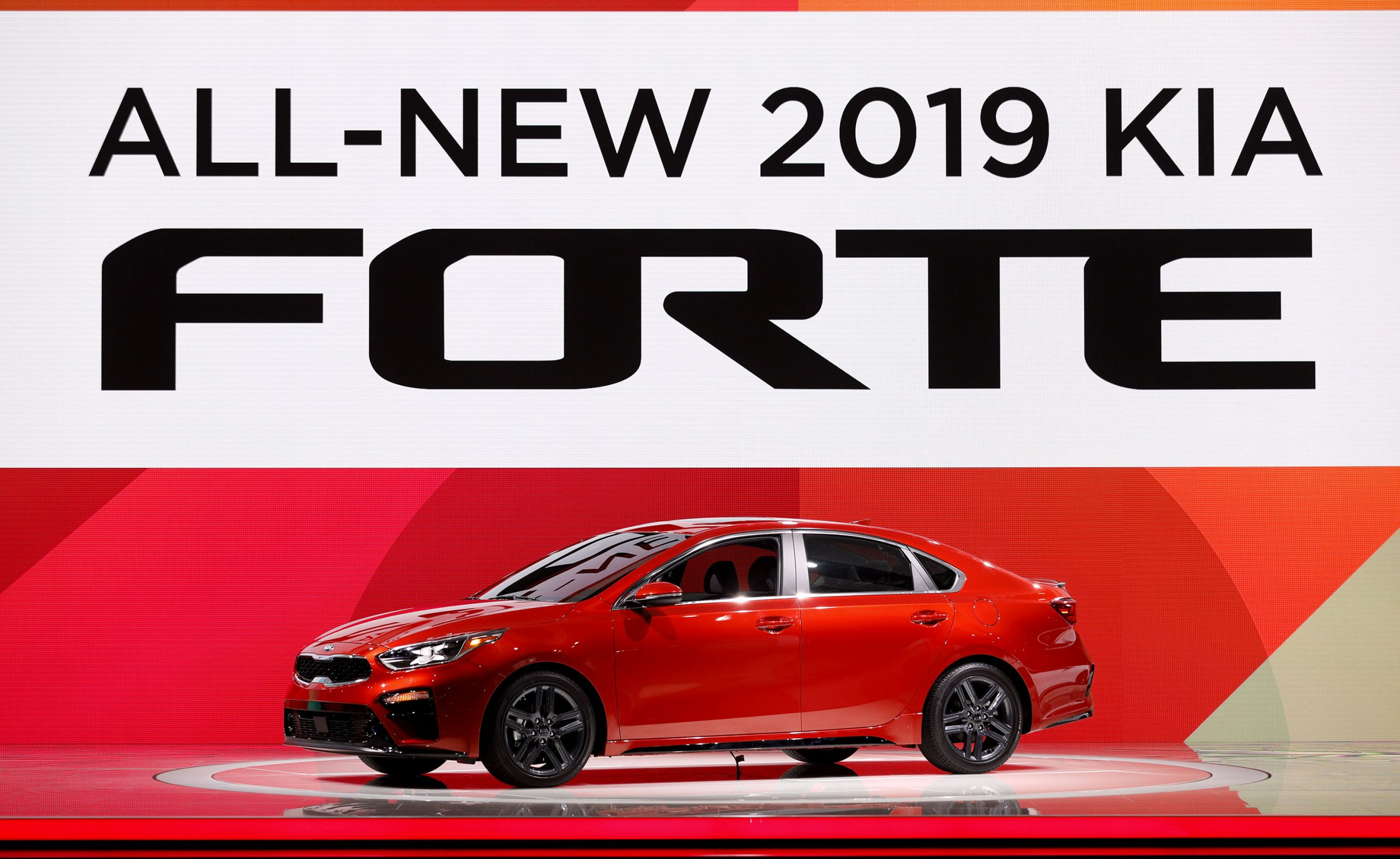 A red 2019 Kia Forte on stage at an auto show shot from the 3/4 angle