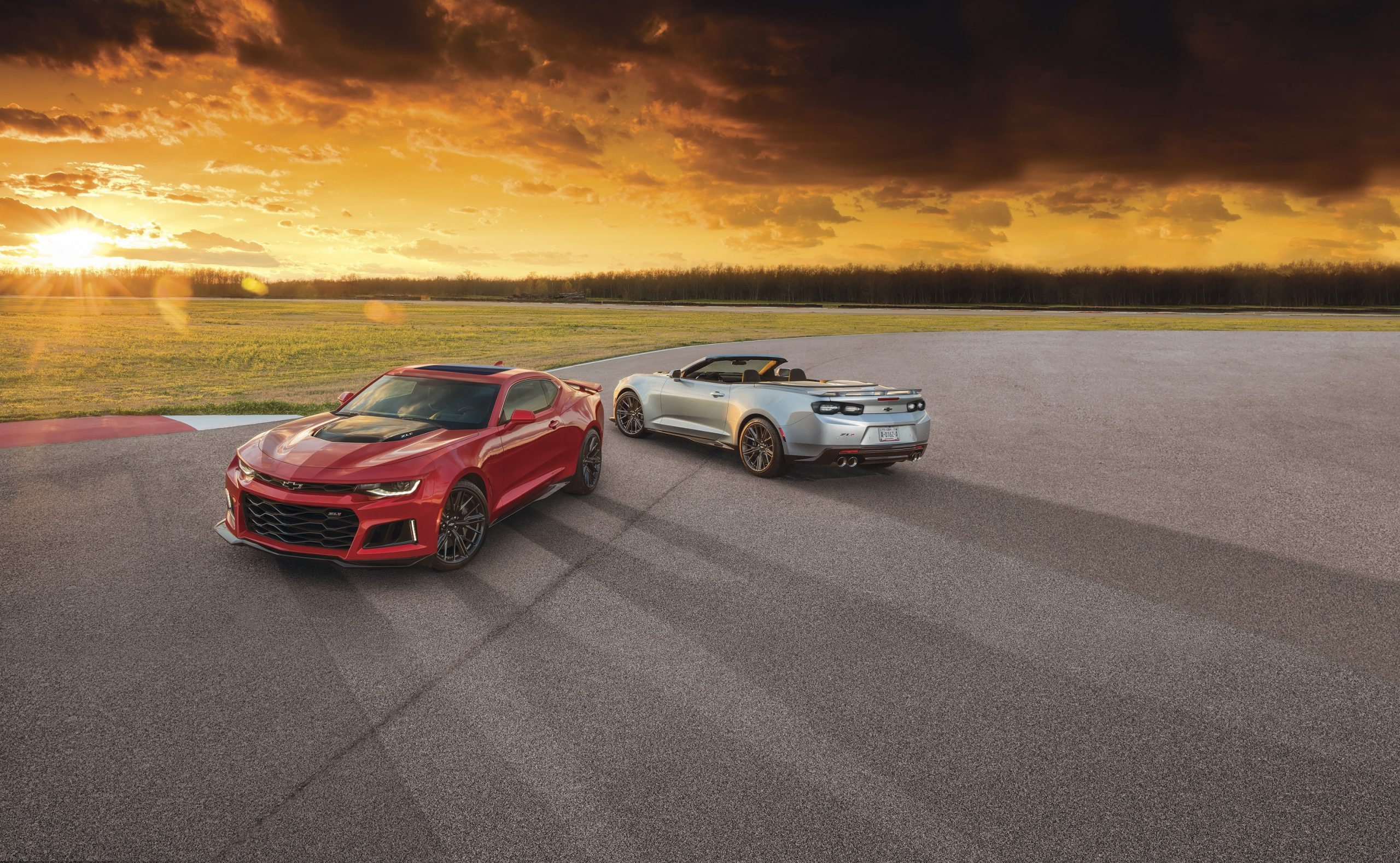A red 2021 Chevrolet Camaro ZL1 coupe and convertible at sunset