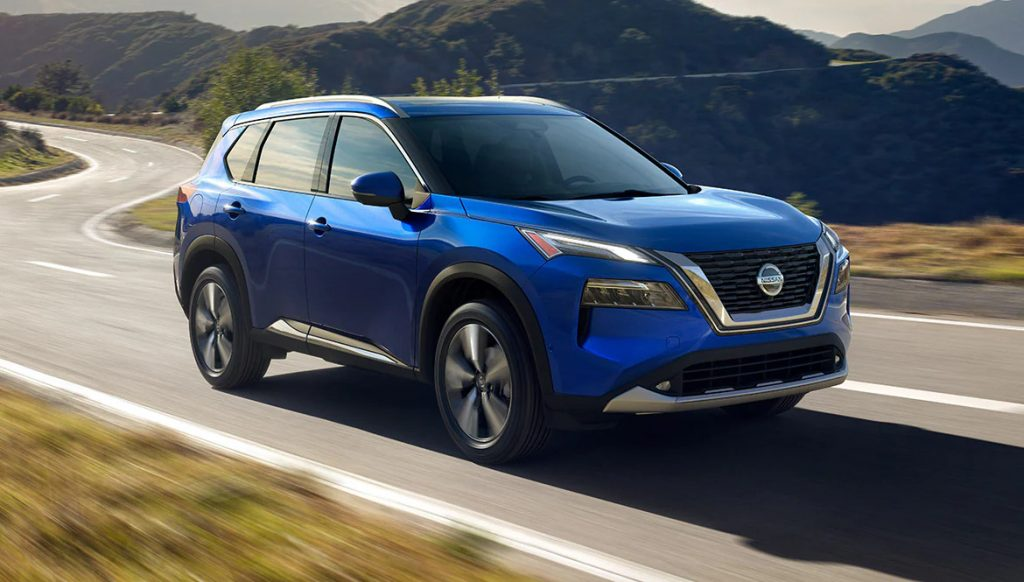 A blue 2021 Nissan Rogue drives on a road