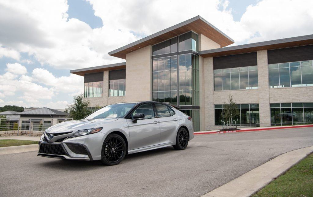 A 2021 Toyota Camry Hybrid XSE in silver sitting in front a nice futuristic building.