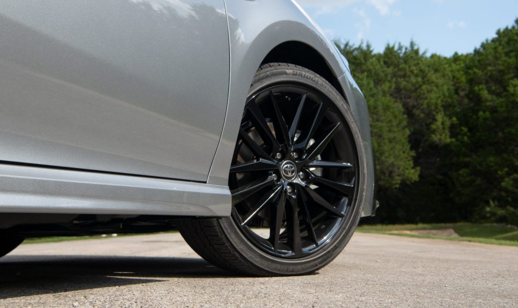 A close up shot of a 2021 Toyota Camry Hybrid XSE black 19-inch wheel