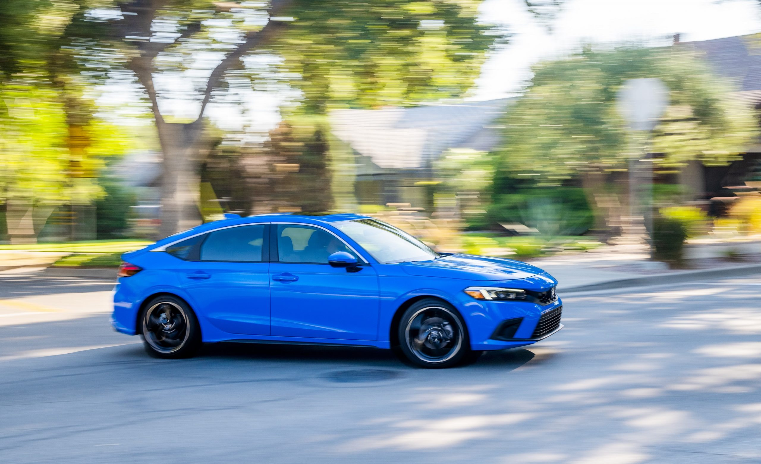 A blue 2022 Honda Civic hatchback shot in profile on a shaded street