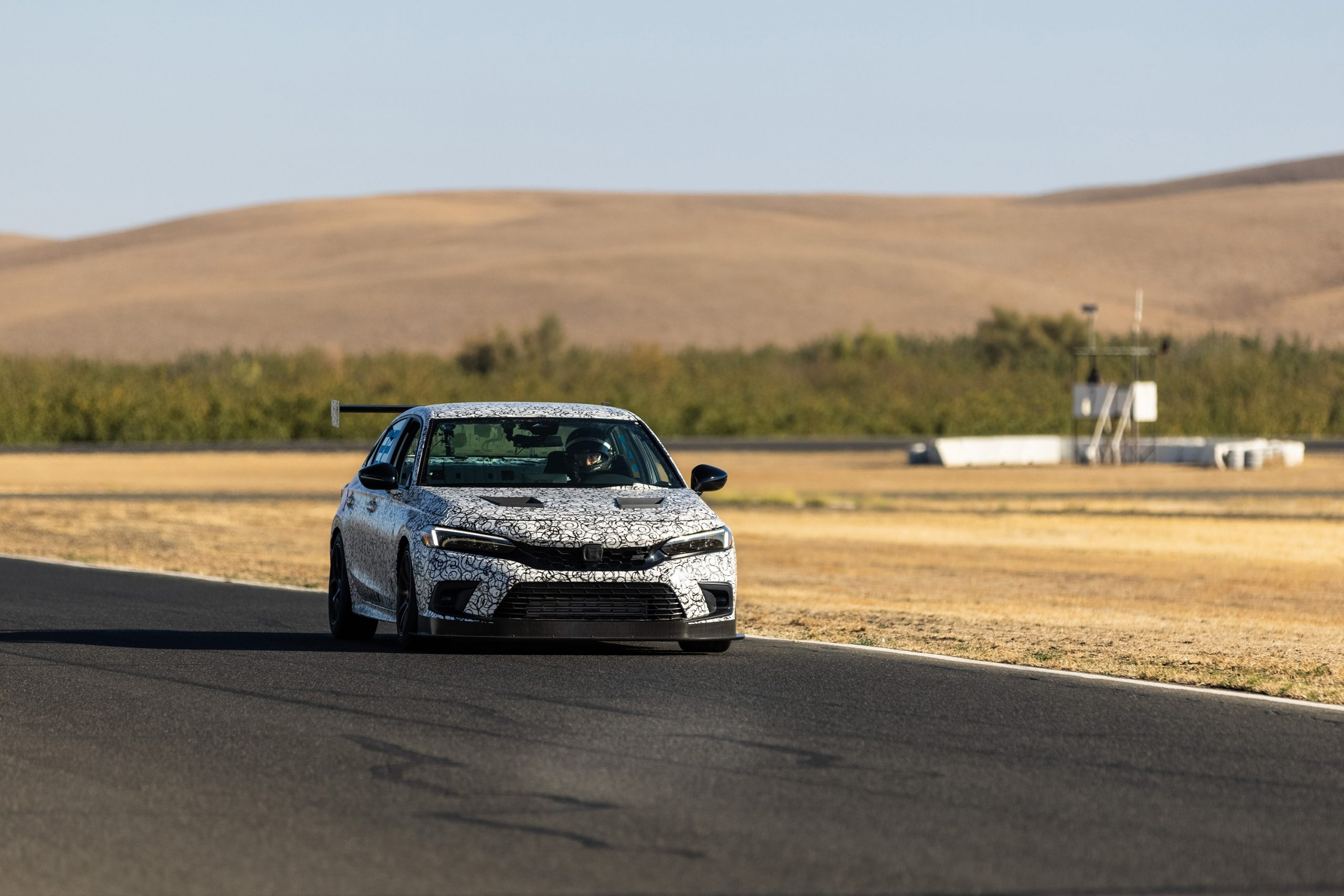 A camouflaged Honda Civic Si makes its way down the straight at a race track