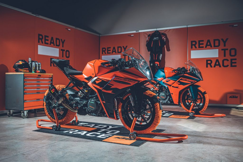 Two orange-and-black 2022 KTM RC 390s with tire warmers on paddock stands in a garage