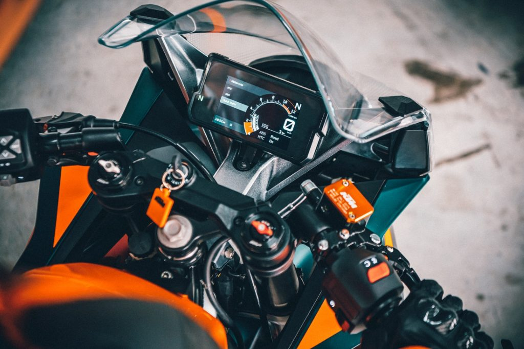 The TFT dash and clip-on handlebars on an orange-and-black 2022 KTM RC 390