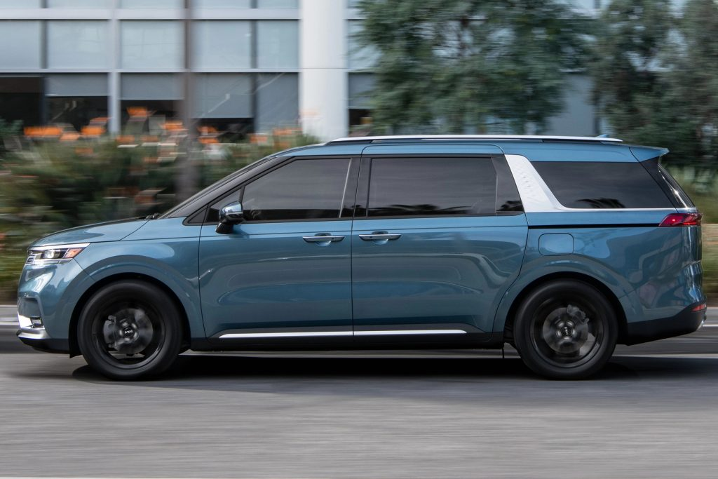 A blue 2022 Kia Carnival is parked on the side of a road