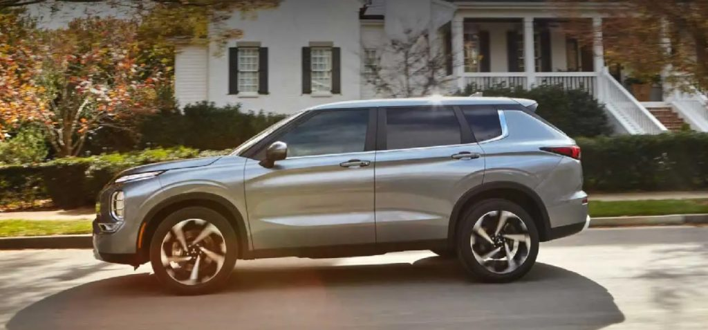 A silver 2022 Mitsubishi Outlander parked in front of a house.