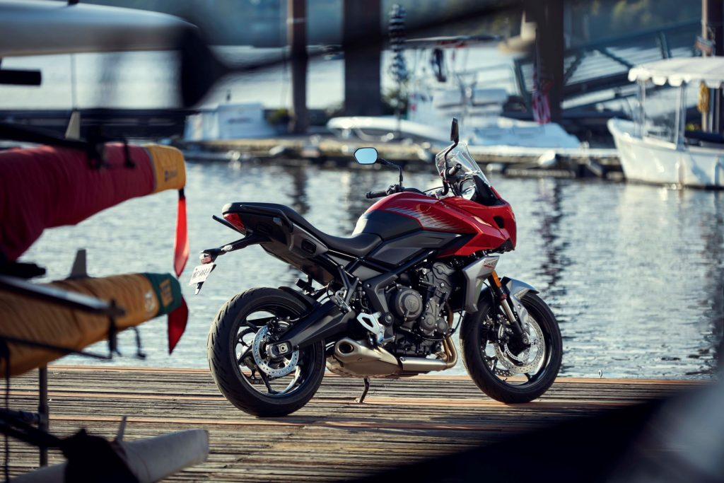 The rear 3/4 view of a red-black-and-silver 2022 Triumph Tiger Sport 660 by some boats on the water