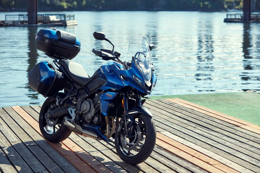 A blue-and-black 2022 Triumph Tiger Sport 660 with accessories by a river
