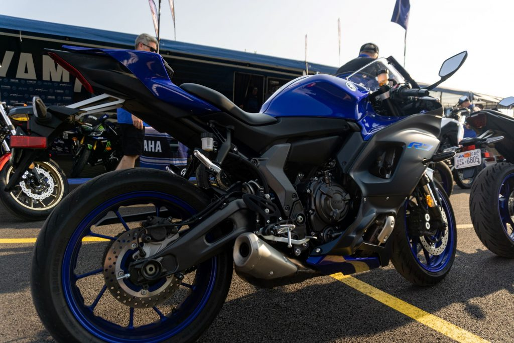 The rear side 3/4 view of a blue-and-black 2022 Yamaha YZF-R7 in a parking lot