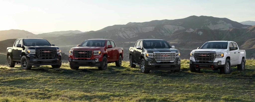 Four GMC pickup trucks parked in front of mountains.