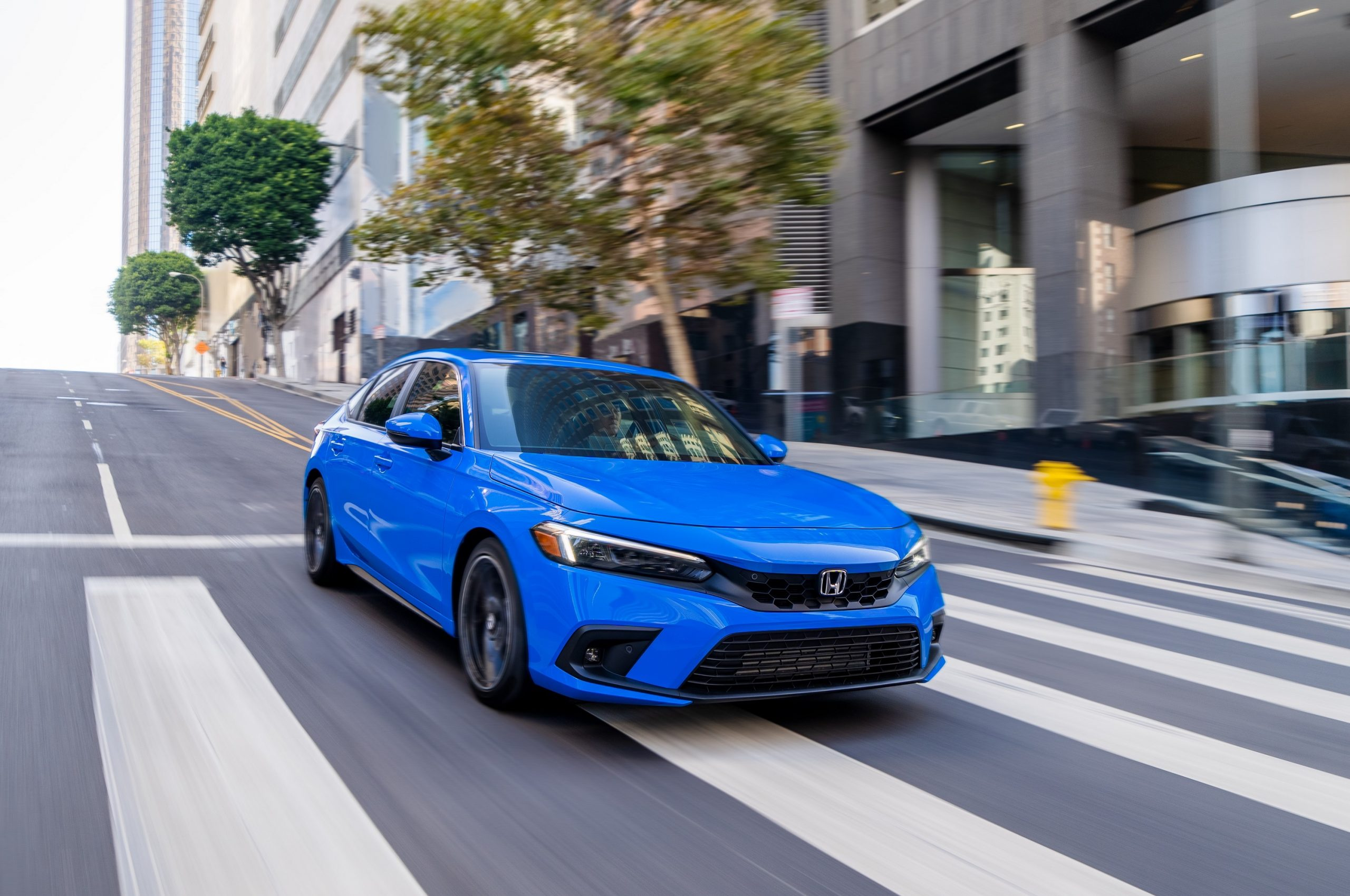 A blue 2022 Honda Civic hatchback shot from the front 3/4 on a city street