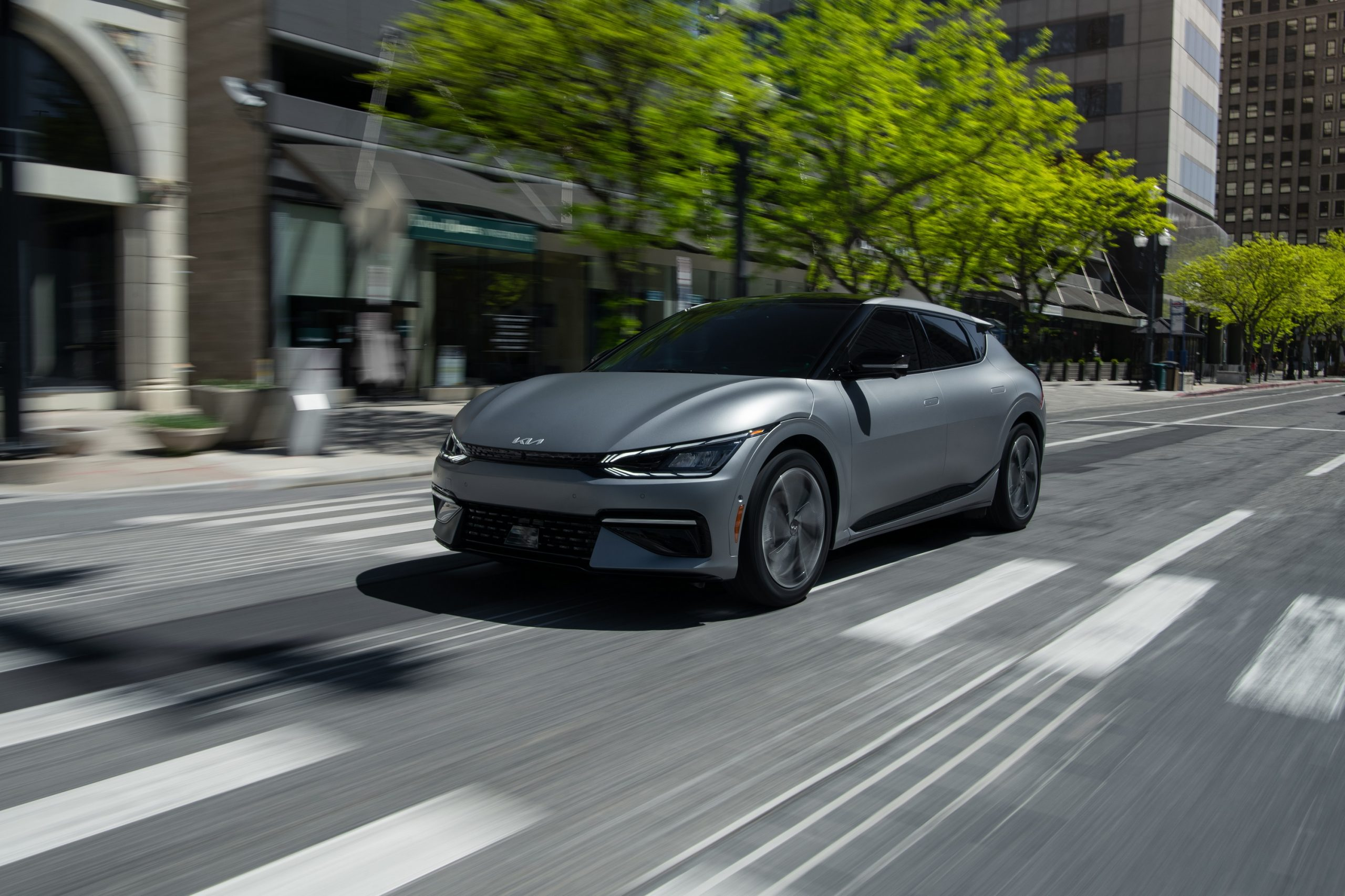 A silver 2022 Kia EV6 rolls down a city street, shot from the 3/4 angle
