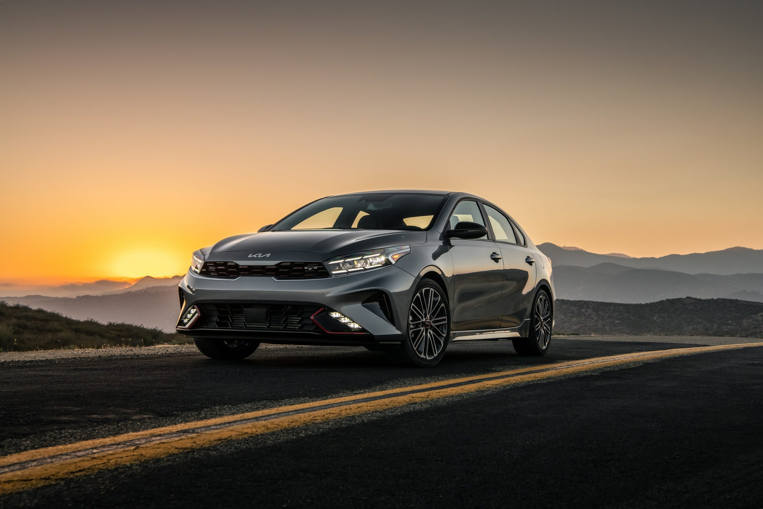 The 2022 Kia Forte GT shot at sunset on a mountain road from the front 3/4 angle