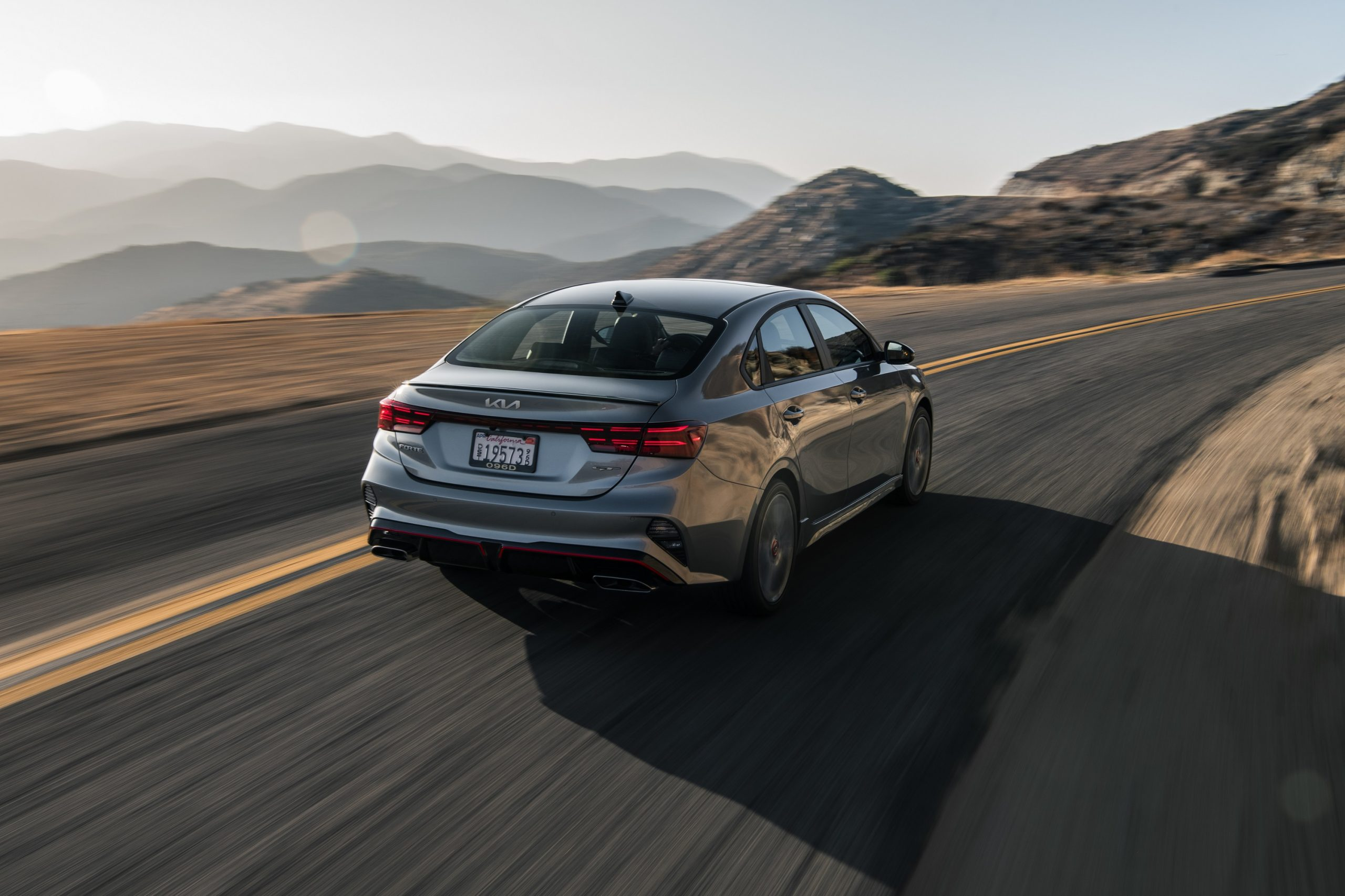 A silver Kia Forte GT shot from the rear on a canyon road